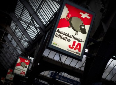 Posters in favour of the referendum at a Zurich train station show a black sheep being kicked off the Swiss flag by a white sheep.