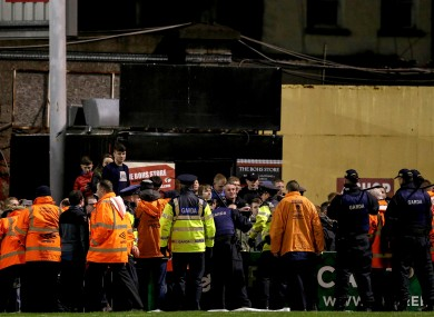 Members of the Gardai hold back Bohs' fans.