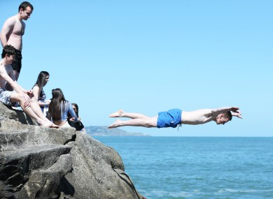 People dive into the sea at the Forty Foot as the sun shines over Dublin.