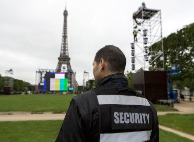 A security guard looks at the Euro 2016 fan zone, under construction on the Champs de Mars in Paris.