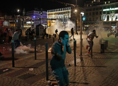 People run after police fire tear gas following clashes after the Euro 2016 soccer championship group B match between England and Russia in Marseille.