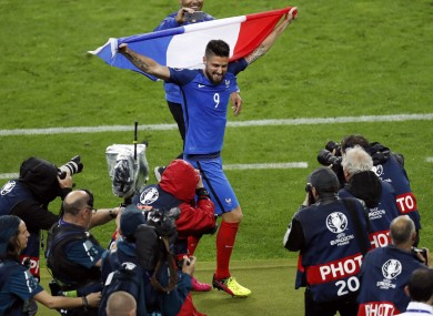 Olivier Giroud celebrates holding his country's national flag at the end of the Euro 2016 quarter-final match between France and Iceland.