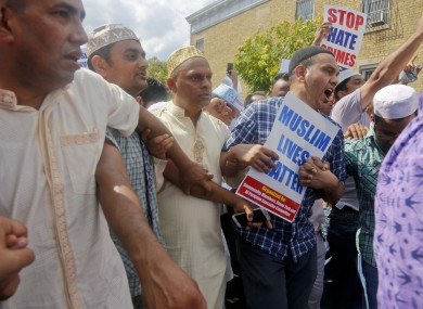 Mourners hold signs and protested near the site of the killings of Imam Maulama Akonjee and Thara Uddin, after funeral services for both men.