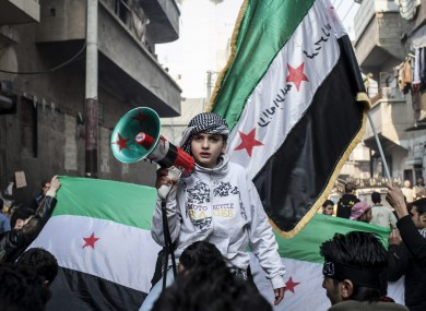 A child uses a megaphone to chant Free Syrian Army slogans during a demonstration in 2013.
