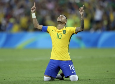 Brazil's Neymar cries as he kneels down to celebrate after scoring the decisive penalty kick during the final match of the men's Olympic football tournament between Brazil and Germany at the Maracana stadium.