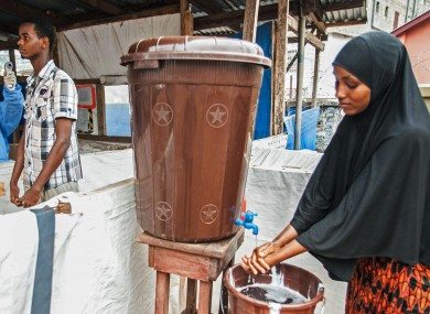 A woman washes her hands as part of Ebola prevention initiative in Freetown, Sierra Leone.