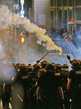 Police fire tear gas early this morning, as protestors converge in Charlotte, North Carolina, after Tuesday's police shooting of Keith Lamont Scott.