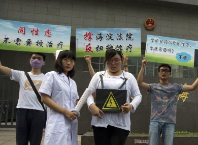 Gay rights campaigners pose for journalists to protest outside a court where the first court case in China involving so-called conversion therapy is held in Beijing, China