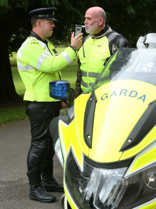 Garda John Cahalin pictured simulating the breathalysing of motorcyclist Stephen Murphy prior to the start of the Road Safety Authority (RSA) Annual Academic Road Safety Lecture.