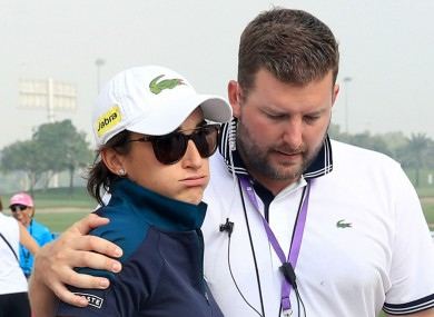 Anne-Lise Caudal is consoled after her caddie collapsed at the Dubai Ladies Masters