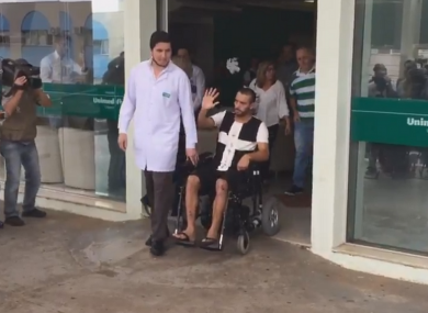 Chapecoense survivor Alan Ruschel waves to the crowd as he leaves hospital.