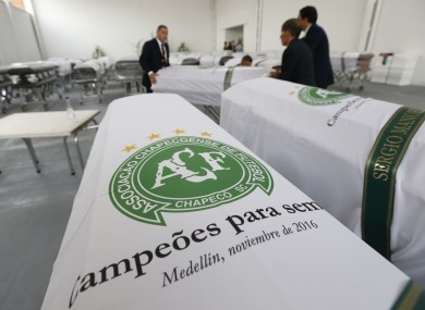 Funeral employees arrange caskets covered in white sheets with a Chapecoense soccer team logo.