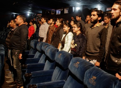 Indian cinema-goers stand during the playing of a national anthem at the KC Cineple in Jammu earlier today.