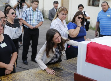 Relatives of Paraguayan Gustavo Encina who died in Monday's plane crash attend the arrival of the coffin, which is covered with a Paraguayan flag, at Silvio Pettirossi airport, Paraguay.