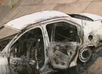 The burned out car found on a slope in a suburban area.