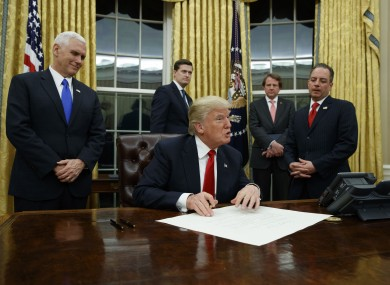 Vice President Pence looks on as Trump signs his first executive order.