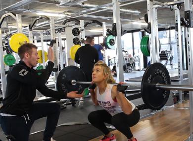 Gareth Barry guides a client through the perfect squat technique.