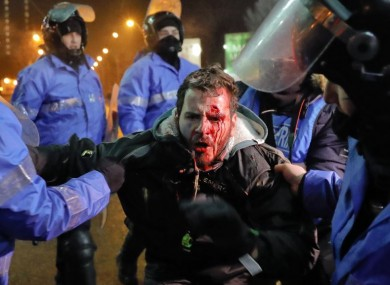 Romanian riot police detain a man after minor clashes erupted during a protest in Bucharest yesterday