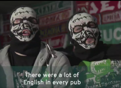 Two Russian hooigans cover their faces with masks.