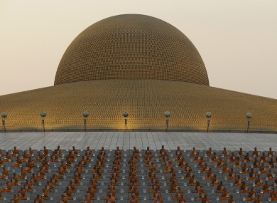 Thai Buddhist monks pray and gather at Wat Dhammakaya temple.