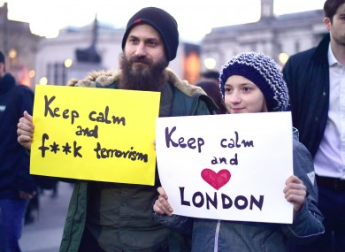 Members of the public hold up signs during the candlelight vigil in Trafalgar Square.