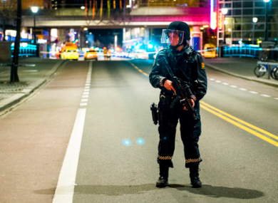 An officer stands guard as police cordon off a large area around a subway station on a busy commercial street.