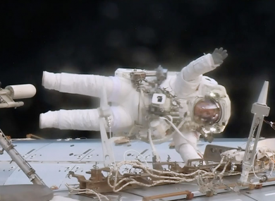 Astronaut Jack Fischer waves while attached to the Destiny laboratory during a spacewalk to replace a failed data relay box and install a pair wireless antennas.