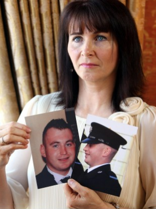 Nuala, mother of murdered Constable Ronan Kerr, holds photos of Ronan.
