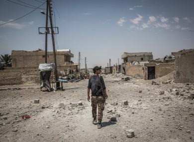 A soldier of the Syrian Democratic Forces (SDF) walks on a street in Al Sinaa neighborhood, eastern Raqqa.