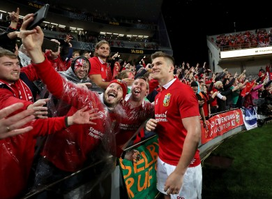 Lions' Owen Farrell poses for a picture with fans after the game.