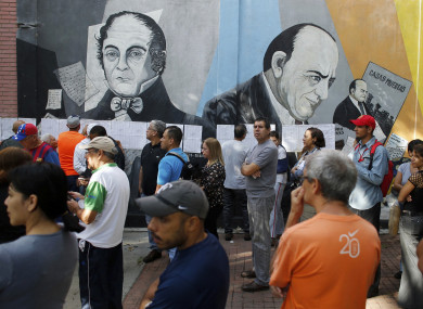 People lineup to enter to a poll station during the election for a constitutional assembly in Caracas, Venezuela