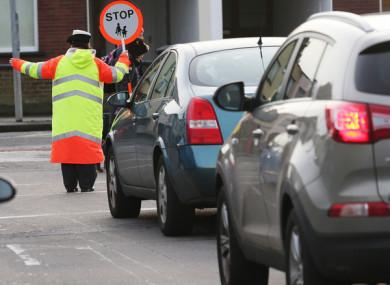 A school traffic warden stops  traffic in Dublin.