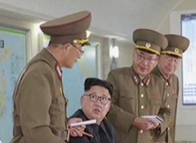 Leader Kim Jong-Un receiving a briefing from generals