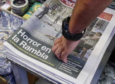 A man touches a newspaper displaying a photograph of the aftermath of the terror attack on Las Ramblas.