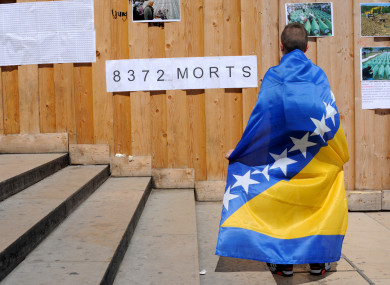 A boy wrapped in a Bosnian flag commemorates the 20th anniversary of the Bosnian war in 2015.