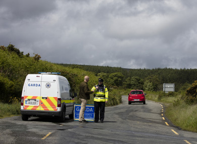 A garda stands at road block to the crime scene where the body parts were found.