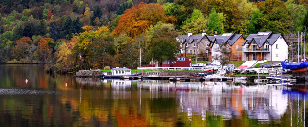 Autumn colours surrounding the village of Kenmore, Perthshire, are reflected in the waters of Loch Tay, Scotland, earlier today