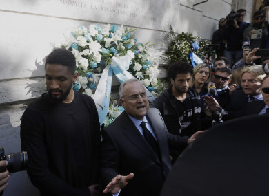 Claudio Lotito (center), accompanied by Lazio players Felipe Anderson (right) and Wallace (left), gives a statement to the press after laying a wreath outside Rome's Synagogue.