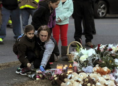 A woman and a little girl leave a bouquet of flowers at a makeshift memorial near Sandy Hook Elementary School in 2012.