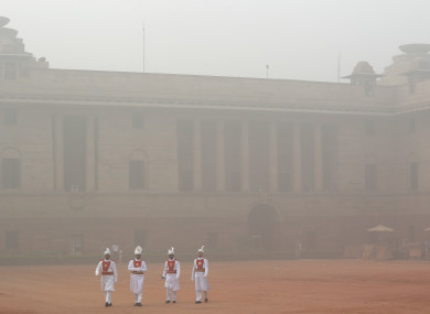 Indian presidential staff members walk surrounded by smog at the presidential palace in New Delhi.