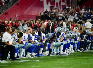 The Dallas Cowboys players, coaches and staff take a knee prior to the national anthem before the game against the Arizona Cardinals.