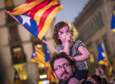 People wave pro-independence flags, outside the Palau de la Generalitat in Barcelona, Spain