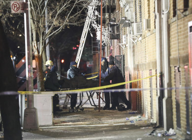 Firefighters work at the site of an apartment fire in Bronx, New York.