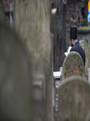 A jewish man prays next to a tomb in the Jewish cemetery in Krakow.