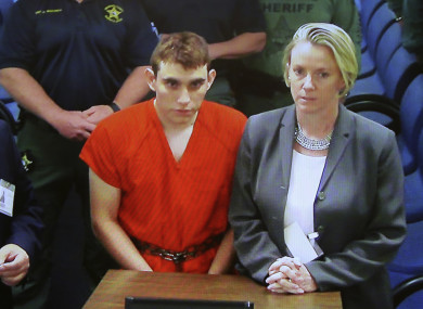 A video monitor shows school shooting suspect Nikolas Cruz, left, making an appearance before Judge Kim Theresa Mollica in Broward County Court.
