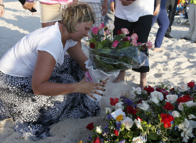 A tourist places places flowers at the scene of the attack in Sousse, Tunisia
