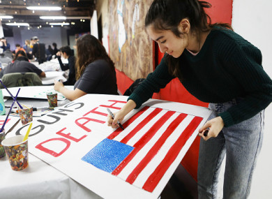 A student paints a sign that will be carried at the March for Our Lives event in Los Angeles