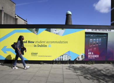A file photo of a person walks past a sign for new student accommodation in Dublin (file photo).