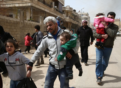 Civilians run for cover from explosions in the city of Afrin in northern Syria today, after Turkish forces and their rebel allies took control of the Kurdish-majority city.