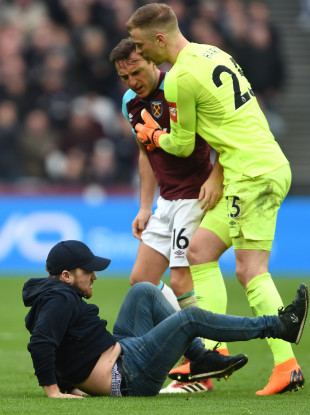 Mark Noble shouts at a West Ham fan after he invaded the pitch today.